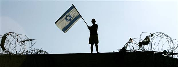 Image: A lone boy holds an Israeli flag atop the roof of the synagogue in the Jewish settlement of Kfar Darom on Friday.